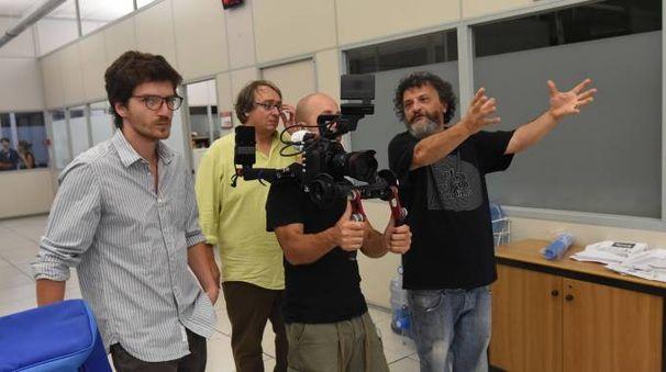 Bob Messini nei panni di un giornalista, si batte un ciak, il regista Marco Manetti al monitor e con gli attori Lorenzo Pedrotti e Messini mentre spiega la scena da girare
