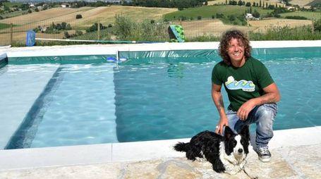 Alessandro Battaglia davanti alla piscina con un ospite a quattrozampe della struttura