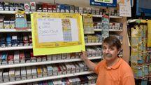 Il titolare della tabaccheria di via Firenze 176 con il cartello che celebra il bel colpo al Gratta e Vinci di un cliente (Fantini)