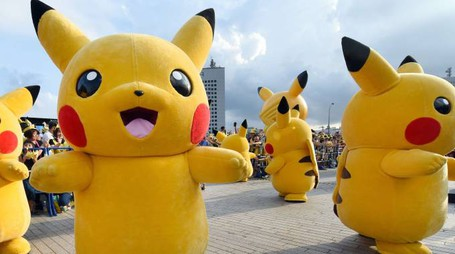 """Dozens of people dressed up as Pikachu, the famous character of Nintendo's videogame software Pokemon, dance with fans as the final of a nine-day """"Pikachu Outbreak"""" event takes place to attract summer vacationers in Yokohama, in suburban Tokyo, on August 16, 2015.       AFP PHOTO / Toru YAMANAKA"""