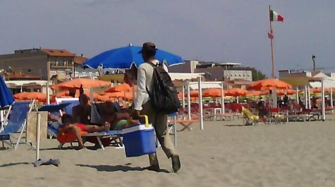 Il venditore con la borsa frigo serve i turisti sulla battigia e poi al bagno