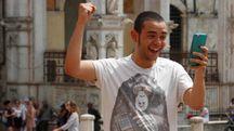 Un giovane gioca a Pokemon Go in piazza del Campo (foto Lazzeroni)
