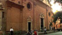 La facciata dell'abbazia di San Pietro. Nel tondo, l'ex parroco, monaco benedettino come l'aggredito, don Gregorio Colosio