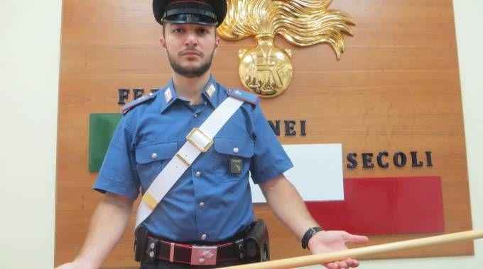 Un carabiniere mostra il manico di scopa con il quale l'uomo ha colpito la 30enne forlivese