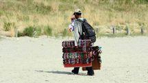 Un vu cumprà in spiaggia (foto d'archivio BusinessPress)