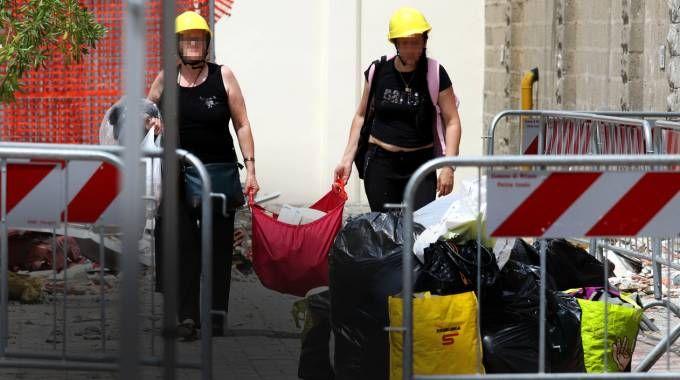 Due residenti portano i loro effetti personali fuori dagli appartamenti evacuati