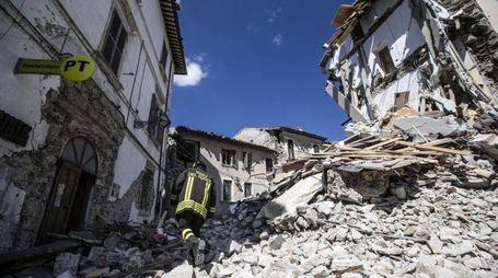 Terremoto, un vigile del fuoco tra le macerie di Arquata (Foto Ansa)