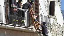 Il recupero di oggetti personali dalle case danneggiate dal terremoto (Afp)