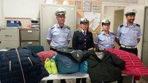 Gli agenti di polizia locale con la merce sequestrata alla fiera