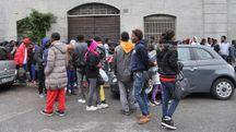 Migranti in coda per il pasto (Newpress)
