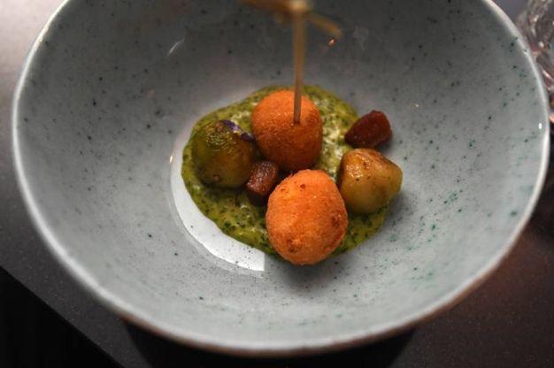 Bon bon di baccalà con stufato di cavoletti, guanciale crispy e salsa verde