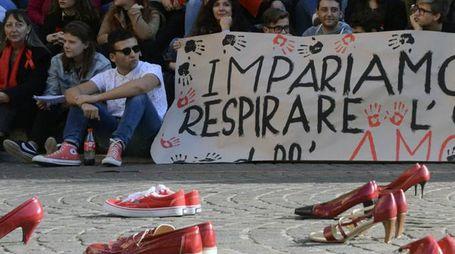 Il momento in cui sono state sistemate in piazza Dante le scarpe rosse diventate simbolo della lotta al femminicidio (Foto Aprili)