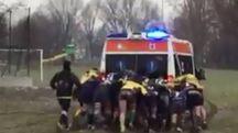 I rugbisti spingono l'ambulanza