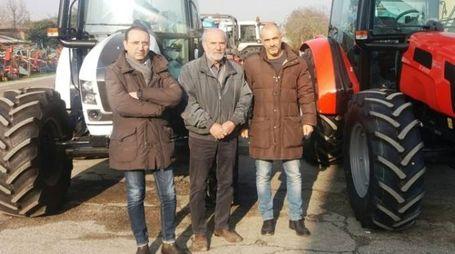 Laerte, Samuele e Emanuele Simoni davanti ai due trattori che i ladri non sono riusciti a rubare