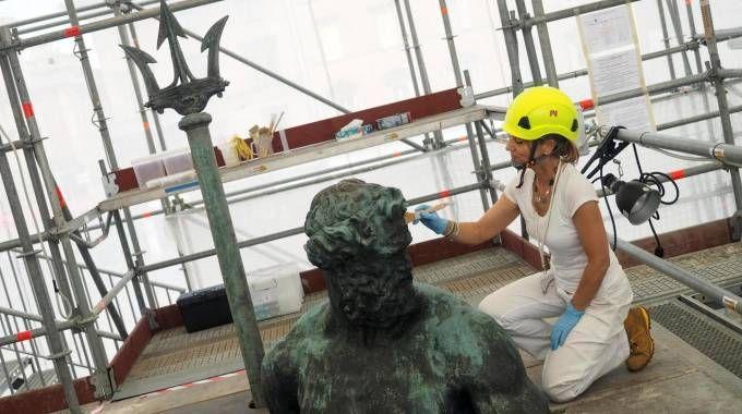 Una restauratrice al lavoro sul volto del Nettuno (fotoSchicchi)