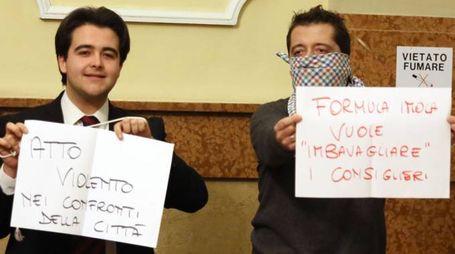 Nicolas Vacchi (Isv) e Simone Carapia (Forza Italia) con i cartelli in consiglio