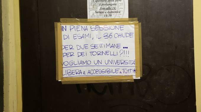 Il cartello affisso fuori dalla biblioteca di Lettere in via Zamboni 36 (Foto Schicchi)