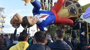 Il mascherone di Gentiloni-Renzi caduto sulla folla che stava assistendo alla prima sfilata (Agostini)
