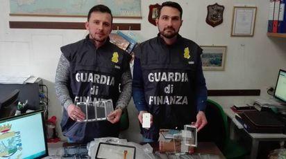 Gli uomini della Guardia di Finanza con i telefonini tarocchi
