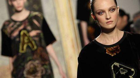 PASSERELLA A sinistra l'omaggio finale delle modelle alla sfilata di Marani: sulla t-shirt ciascuna ha stampata una lettera per comporre il nome 'Angelo Marani' A destra uno degli abiti presentati da Cristiano Burani
