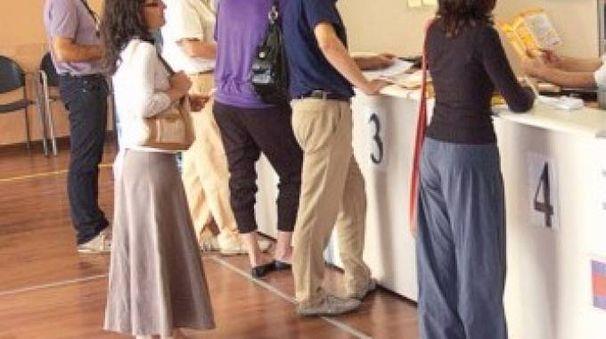 Alcuni cittadini mentre fanno la fila per poter depositare soldi sui propri conti correnti in un ufficio postale