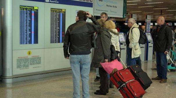 Passeggeri osservano i monitor di servizio a Fiumicino (Ansa)