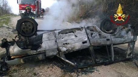 L'auto incendiata nell'incidente di Arcevia. Vigili del fuoco al lavoro