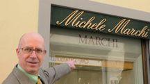 Angelo Marchi indica l'ingresso del suo negozio (foto Alcide)
