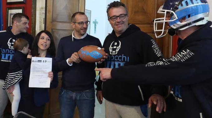 Il presidente Fabbri mentre consegna il pallone col pesce al sindaco