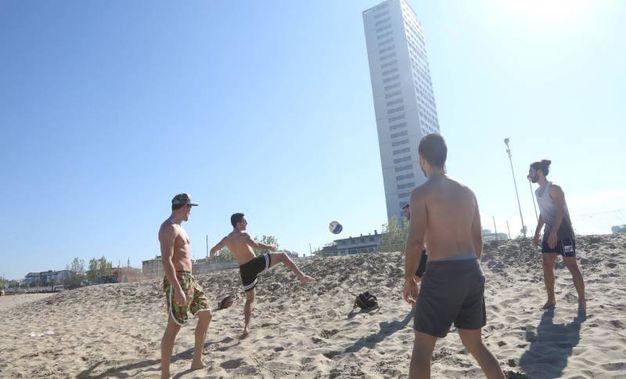 E così, complice anche la bassissima marea, nel pomeriggio tante persone si sono tolte le scarpe, rimboccate i pantaloni e incamminate verso la sabbia bagnata (Foto Ravaglia)
