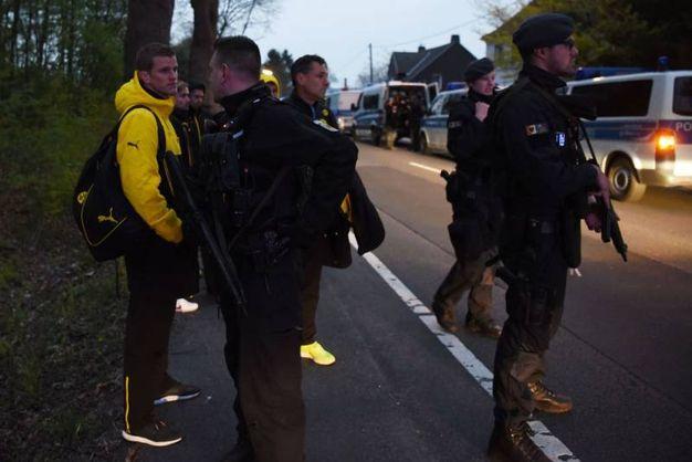 I giocatori con la polizia sopo le esplosioni (Afp)