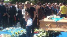 Il funerale di Michele Scarponi, la moglie e i figli accanto al feretro (foto Santini)