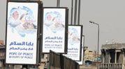 Cartelloni con l'annuncio della visita di Papa Francesco per le vie del Cairo (Ansa)