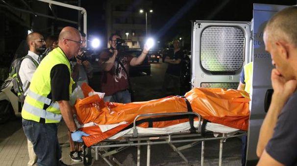 Il corpo del rapinatore portato via dalla gioielleria Ferretti