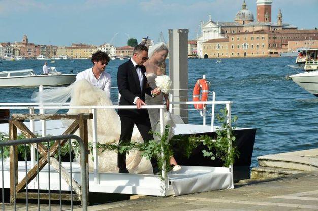 La sposa fasciata in un abito a sirena in pizzo bianco (Lapresse)