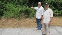 Due residenti della zona indicano il luogo dove dovrebbe sorgere la strada di collegamento per le abitazioni