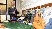 La Guardia di Finanza e alcune delle borse sequestrate (Umicini)