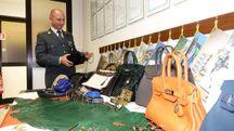 La Guardia di finanza con alcune delle borse sequestrate (Umicini)