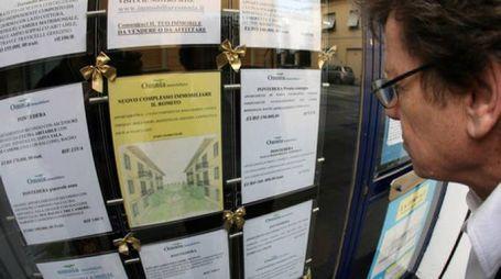 Un uomo guarda la vetrina di un'immobiliare (foto di repertorio, fonte Ansa)