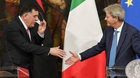 Stretta di mano tra il premier libico al-Serraj e quello italiano Gentiloni (Afp)
