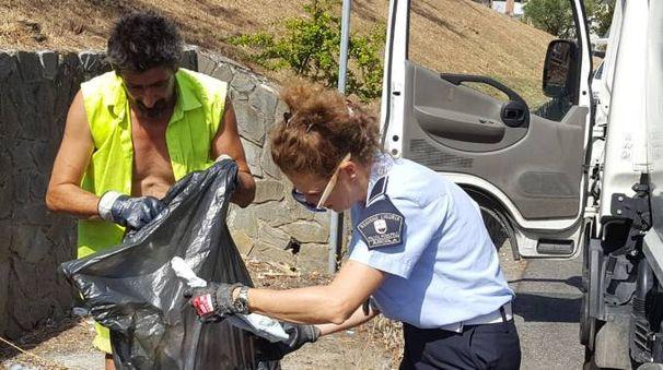 Un'agente della municipale e un operatore Acam cercano indizi degli incivili tra i rifiuti abbandonati