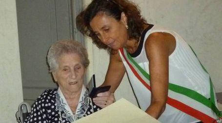 Elide Venturini riceve dalle mani del presidente del consiglio comunale, Ilaria Santi, il gigliato d'argento per i 100 anni raggiunti