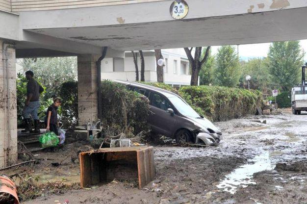 Al lavoro per rimuovere il fango dalle strade di Livorno (Ansa)