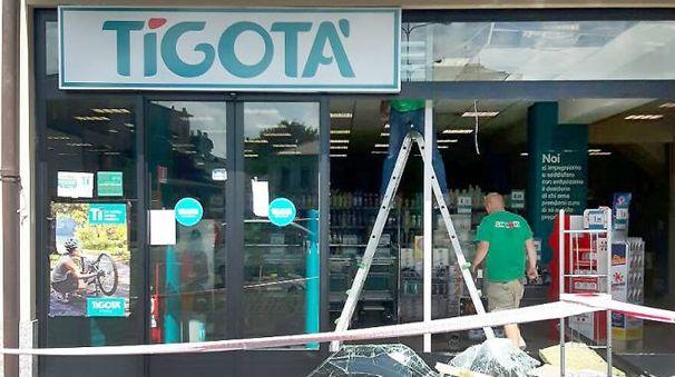 Gli operai sistemano le vetrine dello store preso di mira dalle bande di ladri