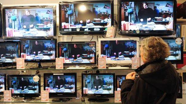 Una signora osserva alcuni televisori (FotoSchicchi)
