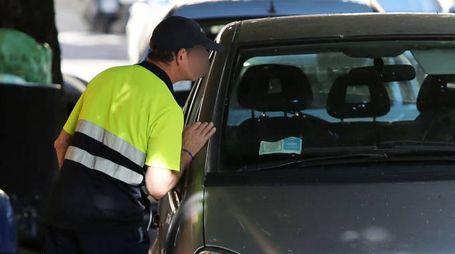 Un operatore Sipa intento a verificare la regolarità del parcheggio di una vettura