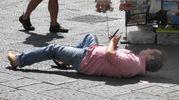 Un turista si sdraia in piazza per fotografare il Duomo di Firenze (New Press Photo)