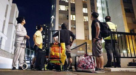 Alcuni residenti lasciano i loro appartamenti a Camden (Ansa)