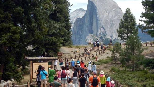 """This August 5, 2015 photo shows tourists walking out to Glacier Point with a background view of Half Dome at Yosemite National Park. A second tourist who visited Yosemite National Park has likely contracted the plague, Californian authorities said. The unnamed individual, from the southern US state of Georgia, had vacationed in Yosemite, the Sierra National Forest and surrounding areas in California early this month. """"Warnings issued in California regarding plague were useful all the way across the country in Georgia,"""" Karen Smith, the director and state health officer for the California Department of Public Health said on August 18, 2015.  AFP PHOTO /FREDERIC J. BROWN"""