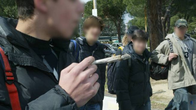 Un ragazzo fuma uno spinello all'uscita di scuola